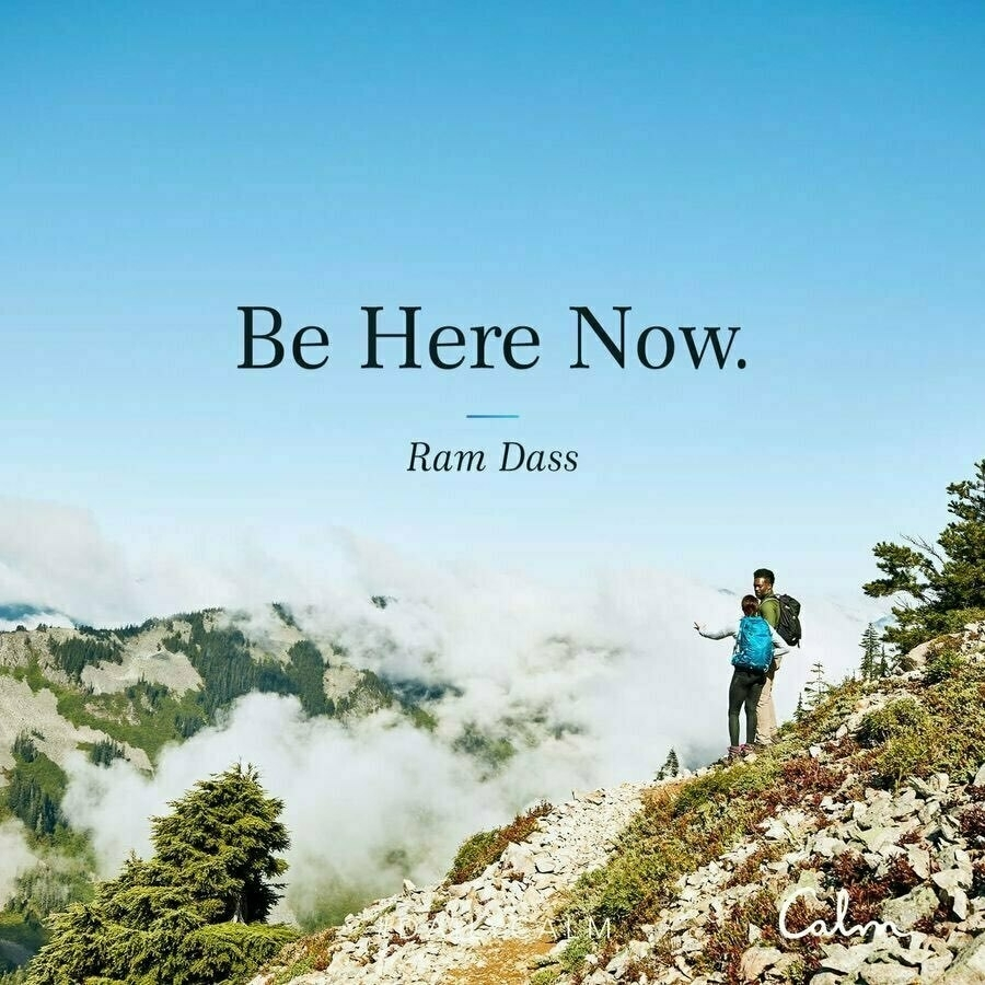 "person hiking on a mountain with the words ""be here now"""