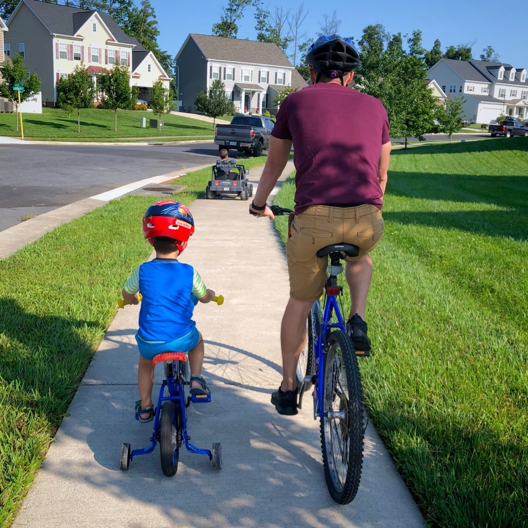 a boy and a man riding bikes beside each other