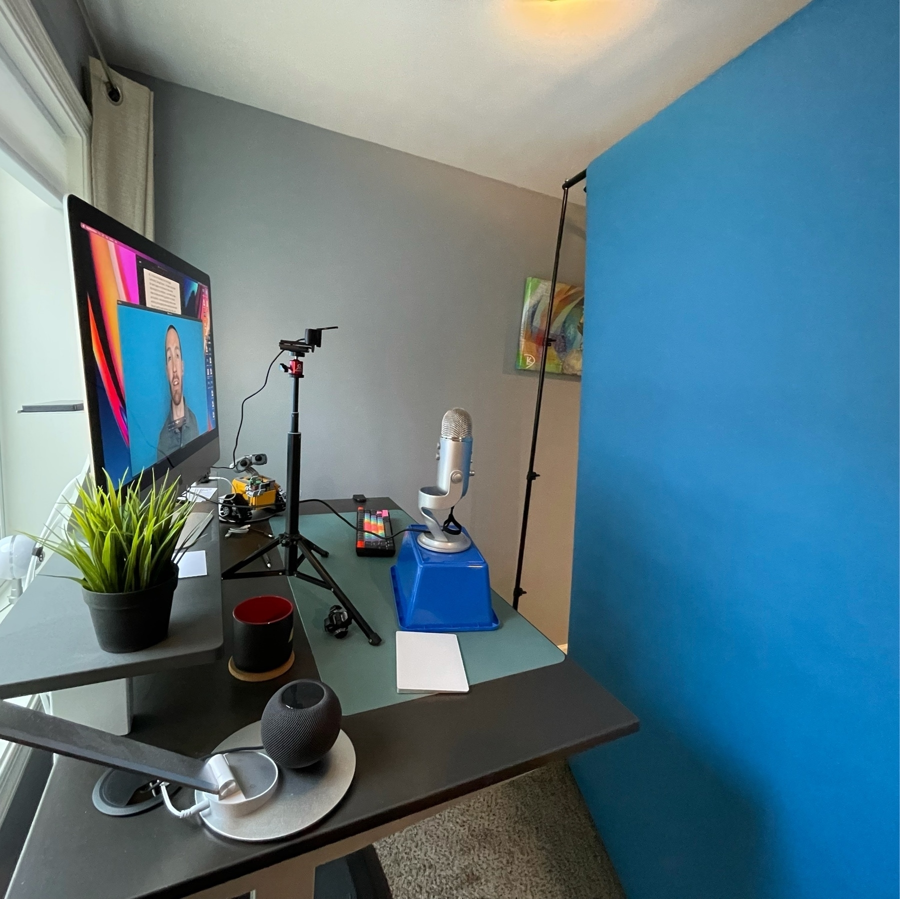 desk set up with computer, webcam, microphone, and blue screen in front of it