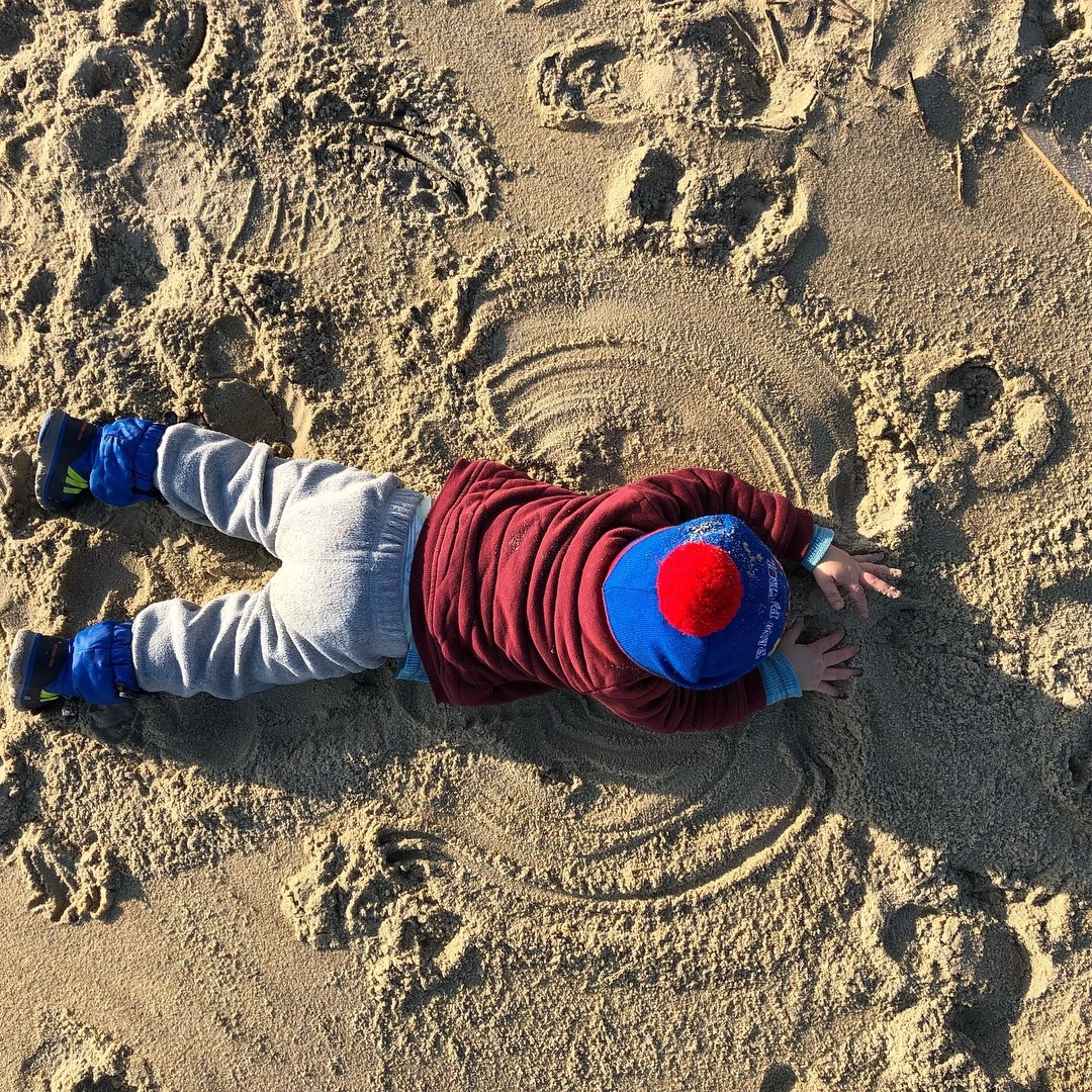 boy laying in the sand